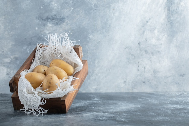 Close up photo of ripe potatoes in wooden basket over grey background