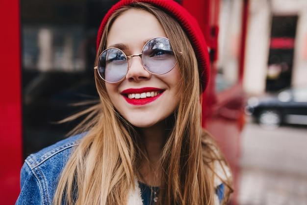 Foto del primo piano della romantica ragazza bianca indossa occhiali rotondi che osserva in su con il sorriso. giovane signora vaga con trucco luminoso che posa accanto al bus rosso.