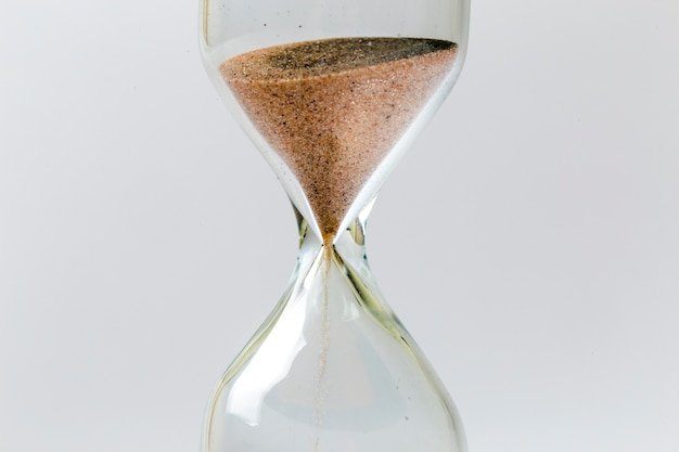 Close up photo of sandglass on gray