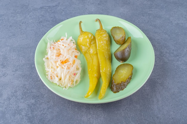 Close up photo of sauerkraut with pepper and cucumber pickle.