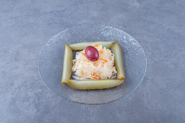 Close up photo of sauerkraut with pickle slices in glass plate.