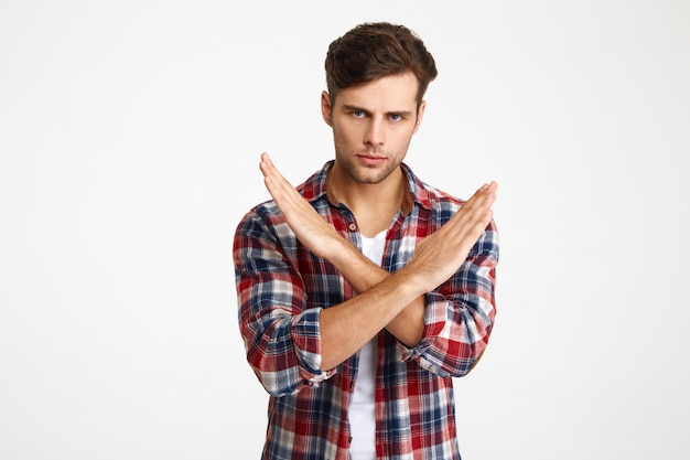 Close-up photo of serious handsome young man showing stop gesture with crossed hands