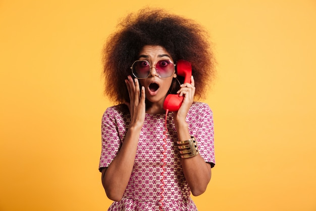 Close-up photo of shocked retro girl with afro hairstyle holding retro phone