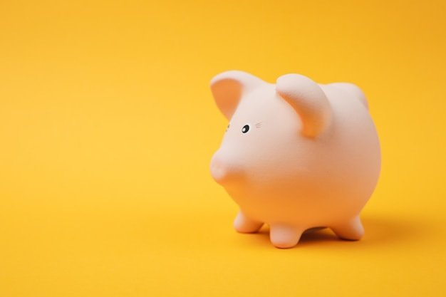 Close up photo, side view of pink piggy money bank isolated on bright yellow wall background. money accumulation investment banking or business services wealth concept. copy space advertising mock up.