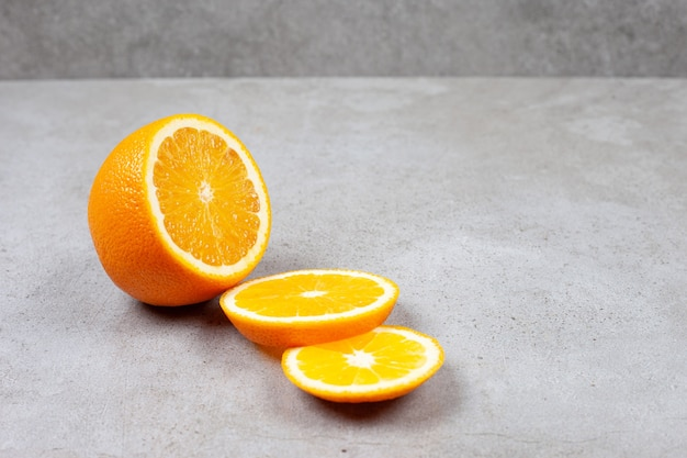 Close up photo of sliced orange on grey table.