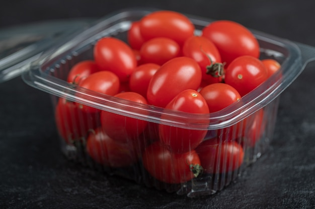 Close up photo of small fresh tomatoes in plastic container. high quality photo