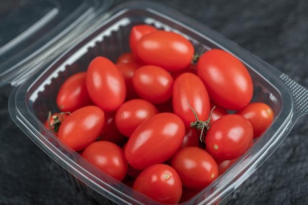 Primo piano foto di piccoli pomodori rossi in un contenitore di plastica. foto di alta qualità