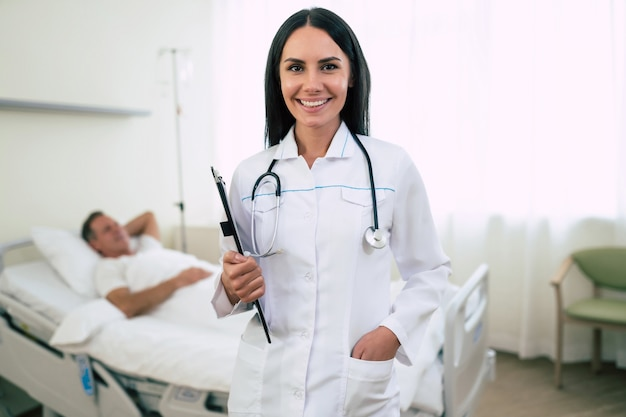 Close up photo of a smiling confident cute woman doctor in a coat with a stethoscope is  with the patient in bed in the