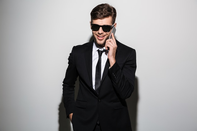Close-up photo of smiling handsome businessman in glasses talking on mobile phone,