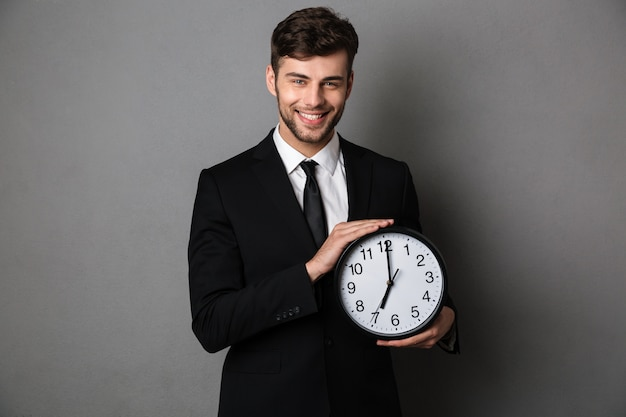 Close-up photo of smiling handsome man in black suit holding clock,