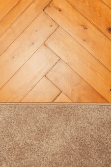 Close up photo some natural wood parquet floor and a little carpet.