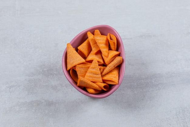 Primo piano foto di patatine piccanti nella ciotola viola.