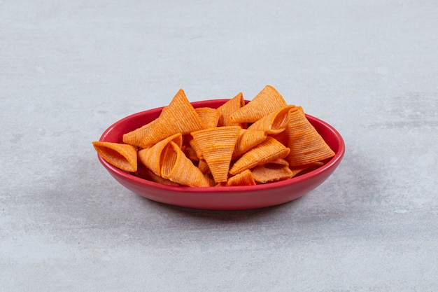 Close up photo of spicy hot chips in red bowl.