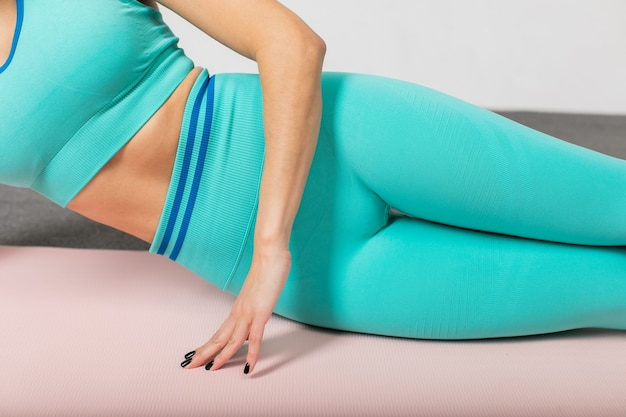 Close up photo of sporty woman in sportswear laying on fitness mat sportsman doing side plank exercise