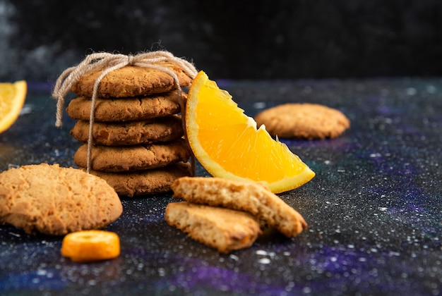 Close up photo of stack of homemade cookies with orange slice over space surface.