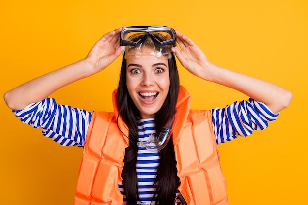 Close up photo of surprised positive girl tourist touch goggles look tourism lifeguard rescue people impressed wear tube mask vest white blue striped shirt isolated yellow color background