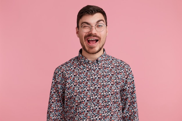 Close up photo of sweet heartbreaking darkhaired attractive man in glasses, flirting with someone, winks showing approval predisposed interes, in coloful shirt, isolated over pinkstudio background