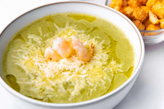 Close up photo of tasty soup creme with spinach parmesan and shrimps