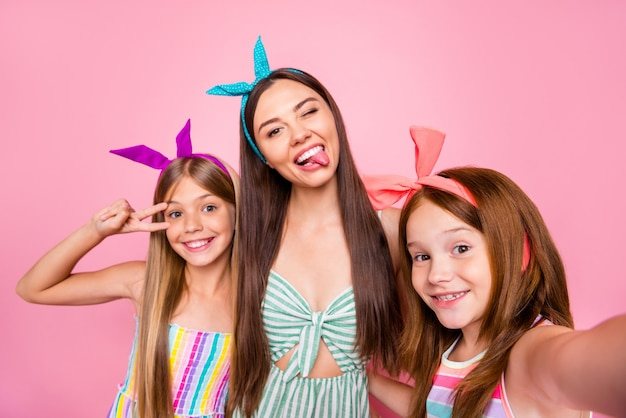 Close up photo of three people with blonde brunette red long haircut make selfie v-signs wear bright headbands dress skirt isolated over pink background