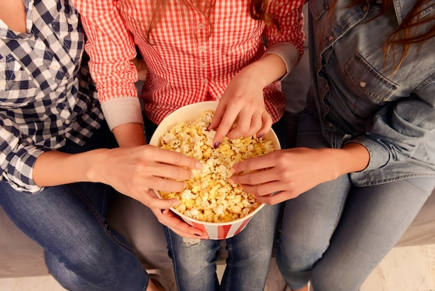 Close up photo of three women sitting on couch and eating popcorn