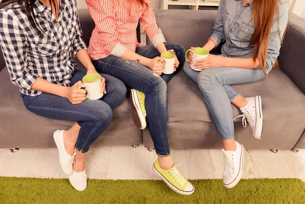 Close up photo of three women sitting on couch with cups