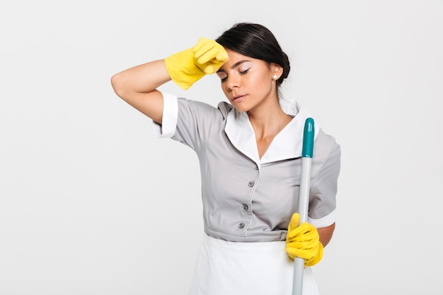 Close-up photo of tired brunette girl in uniform holding mop and wipes sweat from her forehead