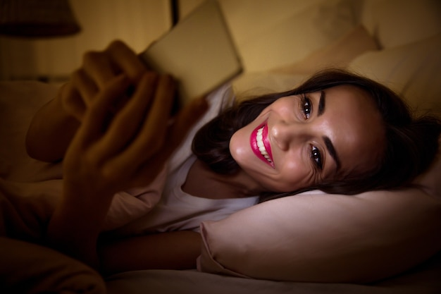 Close-up photo of a tired girl, lying in her bed under the blanket, who is having trouble sleeping because of her internet addiction.