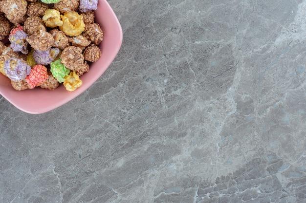 Foto ravvicinata. vista tp di caramelle colorate in ciotola rosa.