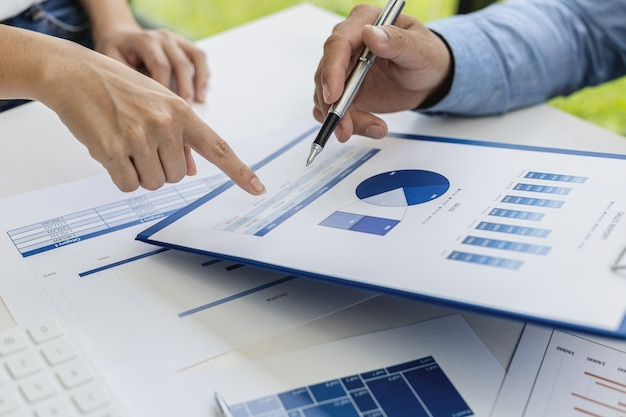 Close-up photo of two businessmen pointing at a sales data sheet in graph format, they are meeting together on the topic of managing sales growth. concept of business cooperation and sales management.