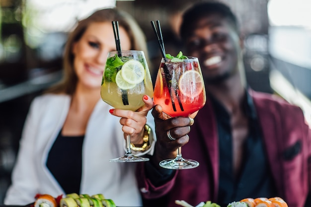 写真をクローズアップ。男性と女性の手に2つのカクテルグラス。マルガリータとモヒートのカクテル