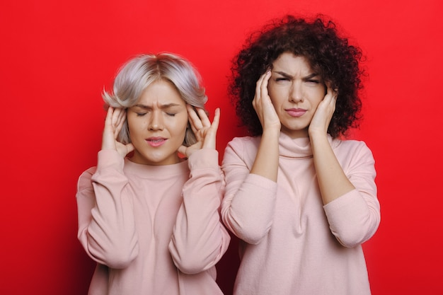 Close up photo of two curly haired women in the same clothes gesturing a headache on red wall
