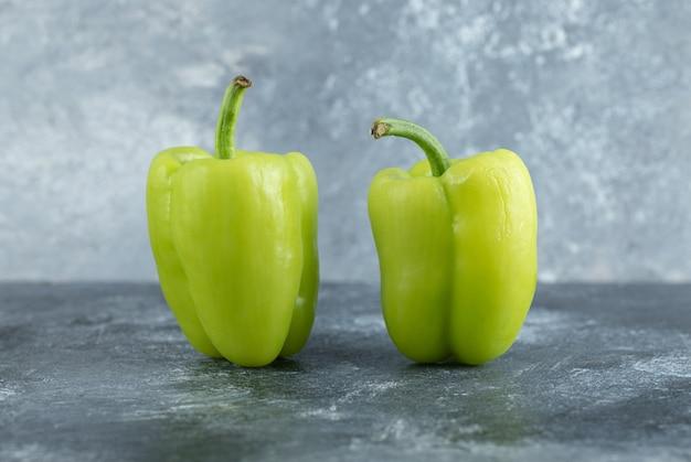 Chiuda sulla foto di due peperoni organici freschi.