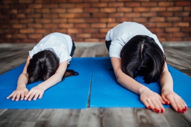 Foto ravvicinata, due ragazze che si rafforzano sul tappetino blu.