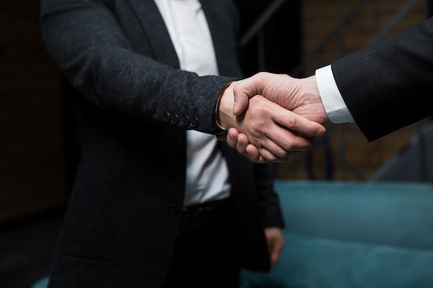 Крупным планом фото двое мужчин в черных деловых костюмах, пожимая руки