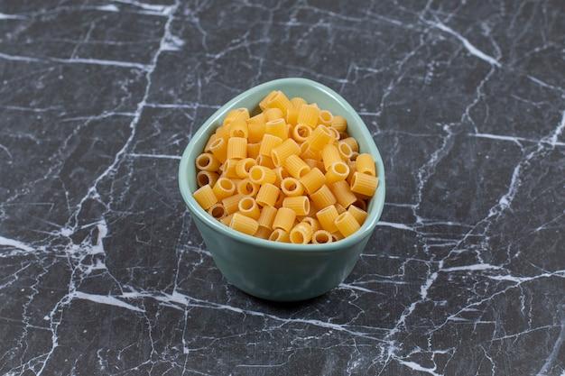 Primo piano foto di pasta cruda nella ciotola blu.