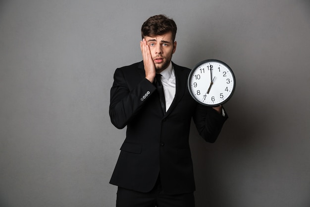 Close-up photo of upset worker in suit holding clock,