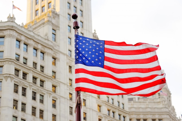 Close up photo of usa flag with skyscraper on background