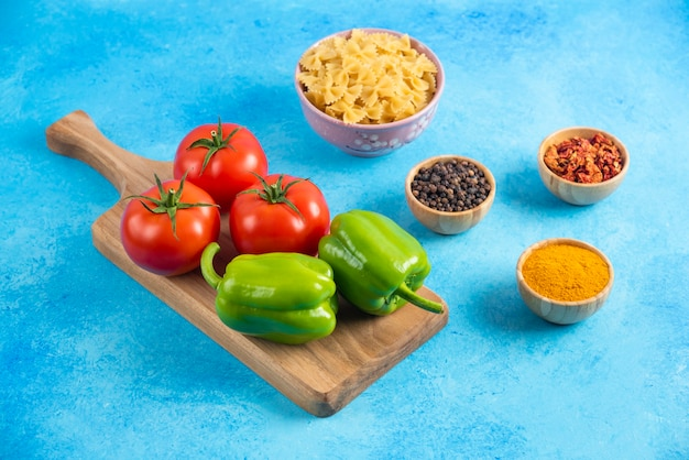 Close up photo of vegetables on wooden board and spices with raw pasta on blue surface.