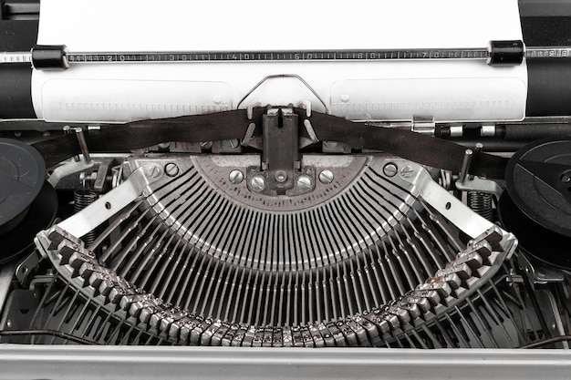 Close-up photo of vintage typewriter with empty paper sheet