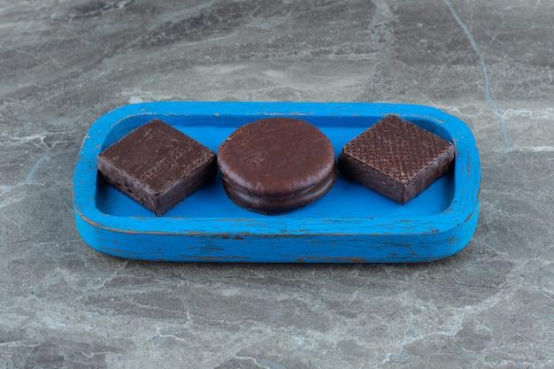 Foto ravvicinata di wafer e cookie su piatto di legno blu.