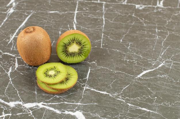Close up photo of whole or sliced kiwis on black
