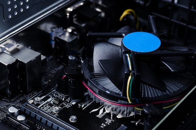 Close up photo with motherboard of computer and its fan.