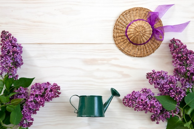 Close up photo with toy watering can, little straw hat and lilac on white wooden background.