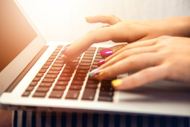 Close up photo of woman hand typing on laptop worker
