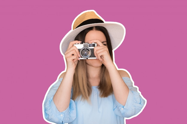 Close up photo of woman in hat on purple taking a photo with retro camera.