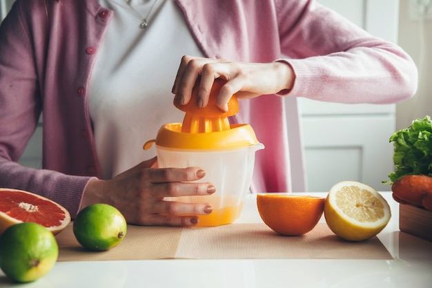 Close up photo of a woman making juice at home out of fruits using a manual squeezer