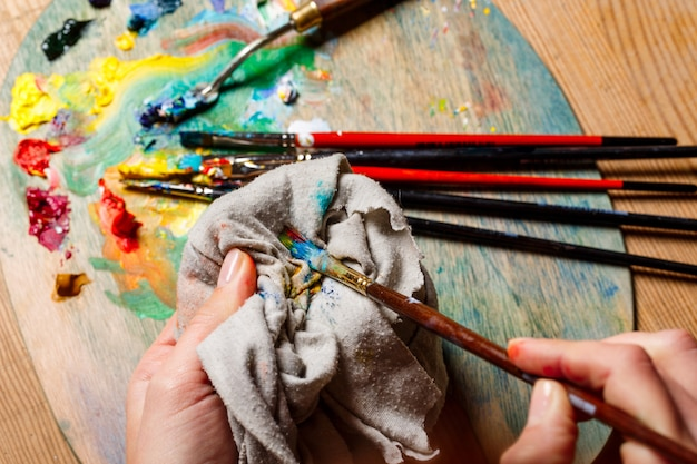 Chiuda sulla foto delle pitture ad olio di miscelazione della donna sulla tavolozza