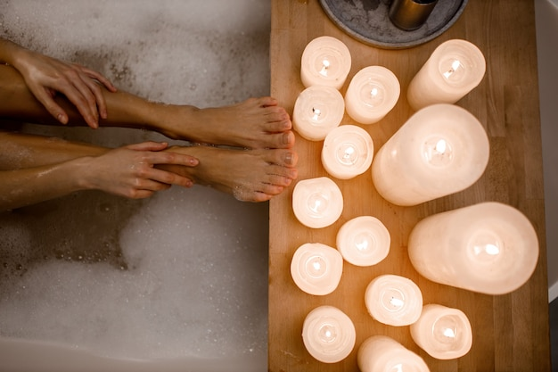 Close up photo of woman's body in spa bathtub with foam and wooden table vase of plant candle. modern spa center.