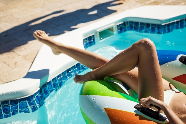 Close up photo of woman's legs in swimming pool