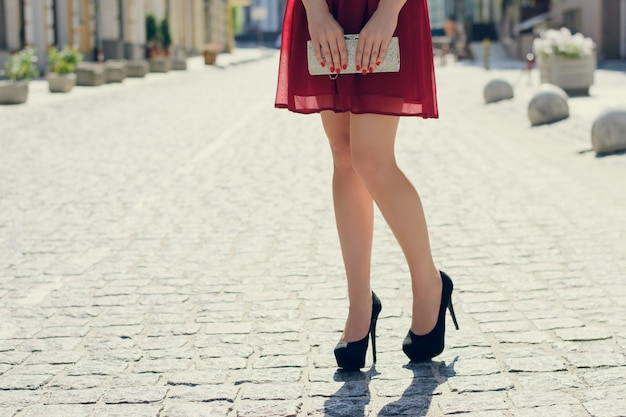 Close up photo of woman's logh legs against view of the city. she is wearing red dress and black high-heels and holding bag in hands
